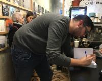 Adrián Morales, alumno del Grado de Periodismo de UDIMA, firma un ejemplar.