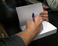 Imagen en detalle de Morales firmando uno de sus libros.